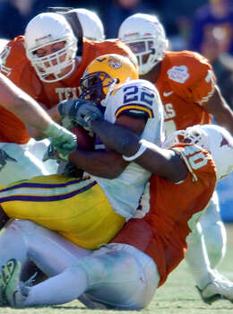 FOR SPORTS - Texas' Cory Redding (40) and teammates gang tackle LSU's LaBrandon Toefield (22) Jan. 1, 2003 during the SBC Cotton Bowl Classic in Dallas, Texas. Texas went on to defeat LSU by a score of 35 -20. PHOTO BY EDWARD A. ORNELAS/STAFF Photo: EDWARD A. ORNELAS, SAN ANTONIO EXPRESS-NEWS / SAN ANTONIO EXPRESS-NEWS