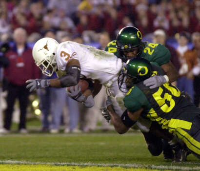 Texas running back Hodges Mitchell (3) drags Oregon's Ryan Mitchell (24) and Michael Callier (50) into the end zone for a touchdown in the second quarter at the Holiday Bowl, Friday, Dec. 29, 2000, in San Diego. Photo: DENIS POROY, AP / AP