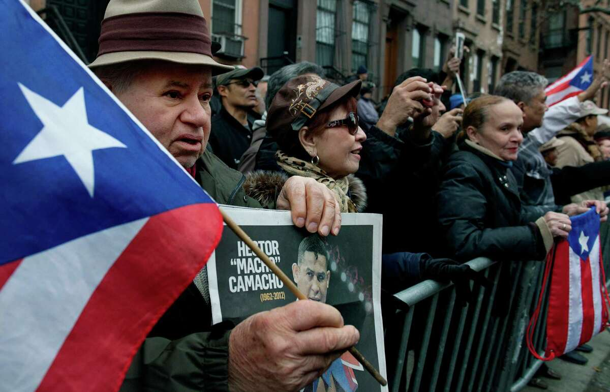 Santiago Manuel, 73, of New York, left, holds the flag of Puerto Rico as he and others gathered at the funeral of Hector