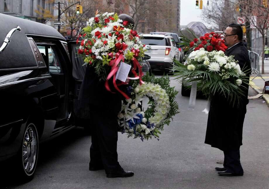 "Flowers from the funeral of Hector ""Macho"" Camacho are taken from St. Cecilia's Roman Catholic Church to the hearse, in New York, Saturday, Dec. 1, 2012. Doctors pronounced Camacho dead on Saturday, Nov. 24, after he was removed from life support at his family's direction. He never regained consciousness after at least one gunman crept up to his car in a darkened parking lot in Puerto Rico and opened fire. Photo: Richard Drew, AP / AP"