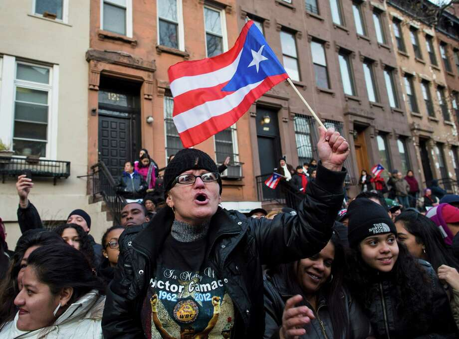 "A supporter of former boxing champion Hector ""Macho"" Camacho waves a Puerto Rican flag outside St. Cecilia's Roman Catholic Church in New York where his wake was being held, Friday, Nov. 30, 2012, in New York. Doctors pronounced Camacho dead on Saturday, Nov. 24, after he was removed from life support at his family's direction. He never regained consciousness after at least one gunman crept up to his car in a darkened parking lot in Puerto Rico and opened fire. Photo: John Minchillo, AP / FR170537 AP"