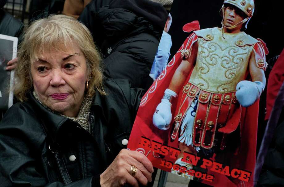 "A woman holds a sign honoring Hector ""Macho"" Camacho outside St. Cecilia's Roman Catholic Church in New York after Camacho's funeral, Saturday, Dec. 1, 2012. Doctors pronounced Camacho dead on Saturday, Nov. 24, after he was removed from life support at his family's direction. He never regained consciousness after at least one gunman crept up to his car in a darkened parking lot in Puerto Rico and opened fire. Photo: Craig Ruttle, AP / FR61802 AP"