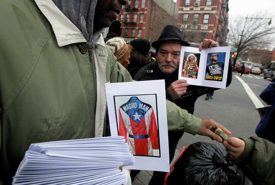 "A vendor sells commemorative photos of Hector ""Macho"" Camacho after his funeral at St. Cecilia's Roman Catholic Church in New York,  Saturday, Dec. 1, 2012. Hundreds mourned Hector Camacho on Saturday in the landmark East Harlem church the fighter attended as a boy, and hundreds more cheered and shouted ""Macho"" when his coffin was carried out and loaded into a hearse afterward. Photo: Richard Drew, AP / AP"