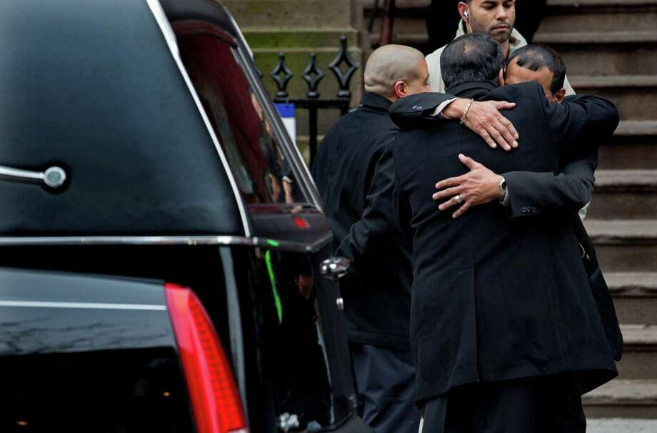 "Mourners hug near a hearse carrying Hector ""Macho"" Camacho's casket near the steps of St. Cecilia's Roman Catholic Church in New York for a funeral, Saturday, Dec. 1, 2012. Doctors pronounced Camacho dead on Saturday, Nov. 24, after he was removed from life support at his family's direction. He never regained consciousness after at least one gunman crept up to his car in a darkened parking lot in Puerto Rico and opened fire. Photo: Craig Ruttle, AP / FR61802 AP"