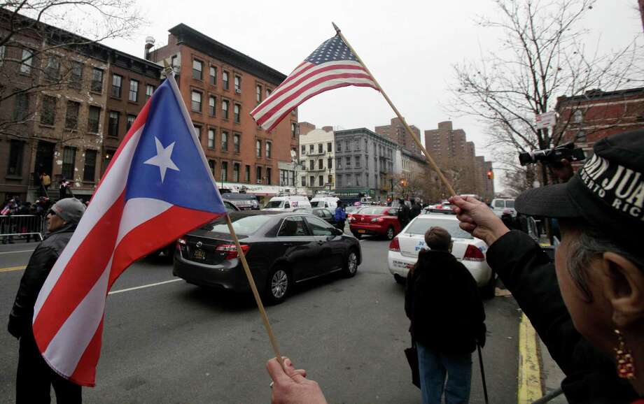 "A woman waves a Puerto Rican and U.S. flag during the procession for the funeral of Hector ""Macho"" Camacho at St. Cecilia's Roman Catholic Church, in New York,  Saturday, Dec. 1, 2012. Doctors pronounced Camacho dead on Saturday, Nov. 24, after he was removed from life support at his family's direction. He never regained consciousness after at least one gunman crept up to his car in a darkened parking lot in Puerto Rico and opened fire. Photo: Richard Drew, AP / AP"