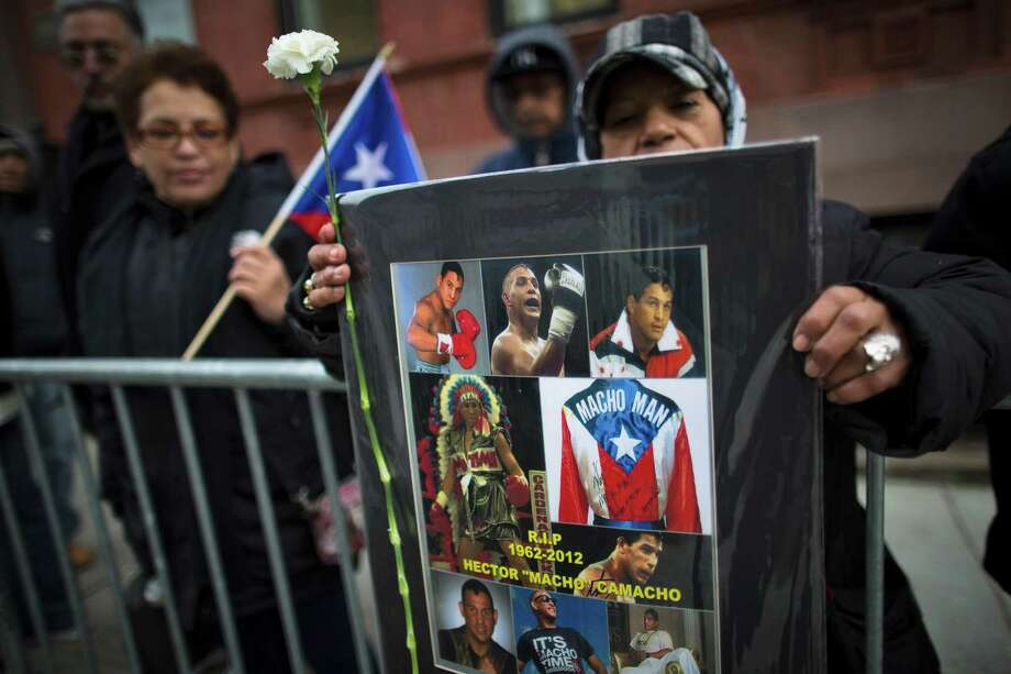 "Irene Huertas, of Manhattan, holds a sign commemorating former boxing champion Hector ""Macho"" Camacho outside St. Cecilia's Roman Catholic Church in New York, where his wake was being held, Friday, Nov. 30, 2012, in New York. Doctors pronounced Camacho dead on Saturday, Nov. 24, after he was removed from life support at his family's direction. He never regained consciousness after at least one gunman crept up to his car in a darkened parking lot and opened fire. Photo: John Minchillo, AP / FR170537 AP"