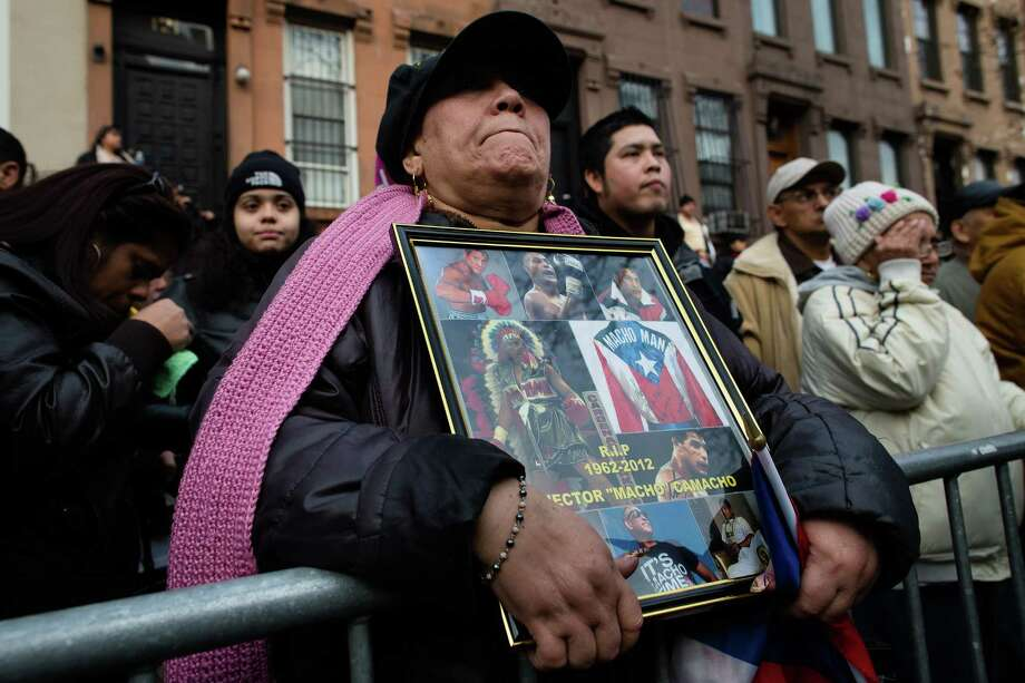 "Eva Ramos, of New York, holds a sign in honor of former boxing champion Hector ""Macho"" Camacho outside St. Cecilia's Roman Catholic Church in New York, where his wake was being held, Friday, Nov. 30, 2012, in New York. Doctors pronounced Camacho dead on Saturday, Nov. 24, after he was removed from life support at his family's direction. He never regained consciousness after at least one gunman crept up to his car in a darkened parking lot in Puerto Rico and opened fire. Photo: John Minchillo, AP / FR170537 AP"