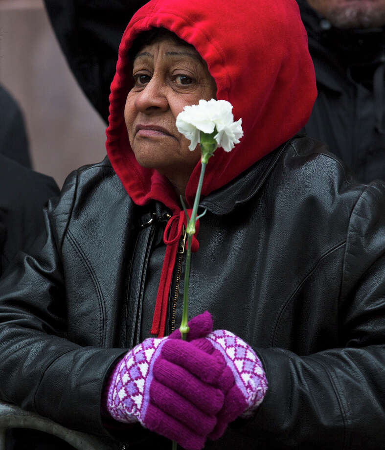 "A mourner holds a flower as she waits to visit former boxing champion Hector ""Macho"" Camacho's casket at St. Cecilia's Roman Catholic Church in New York where a wake was being held, Friday, Nov. 30, 2012. Doctors pronounced Camacho dead on Saturday, Nov. 24, after he was removed from life support at his family's direction. He never regained consciousness after at least one gunman crept up to his car in a darkened parking lot in Puerto Rico and opened fire. Photo: John Minchillo, AP / FR170537 AP"