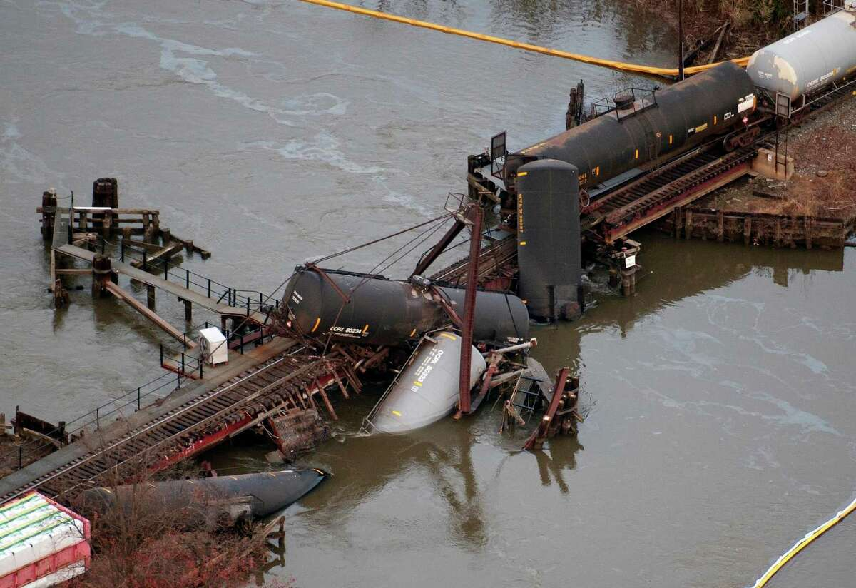 Derailed freight train cars lay in water in Paulsboro, N.J., Friday, Nov. 30, 2012. People in three southern New Jersey towns were told Friday to stay inside after the freight train derailed and several tanker cars carrying hazardous materials toppled from a bridge and into a creek.