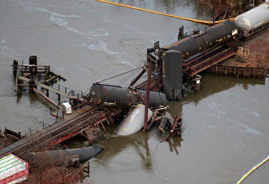 Derailed freight train cars lay in water in Paulsboro, N.J., Friday, Nov. 30, 2012. People in three southern New Jersey towns were told Friday to stay inside after the freight train derailed and several tanker cars carrying hazardous materials toppled from a bridge and into a creek. Photo: Cliff Owen, AP / FR170079 AP