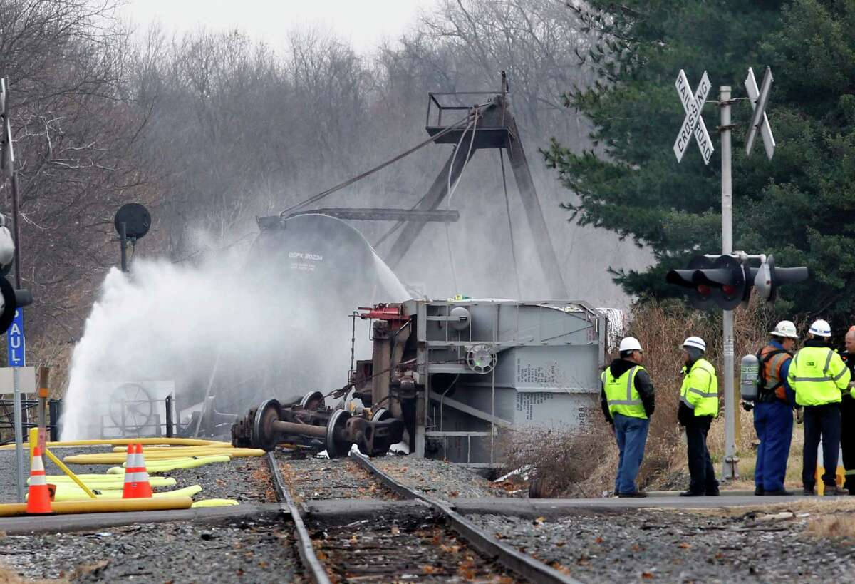 Crews continue to spray water on derailed freight train tank cars in Paulsboro, N.J., Saturday, Dec. 1, 2012, after seven cars of an 84-car freight train with two locomotives derailed earlier Friday. A signal may have been malfunctioning on a southern New Jersey bridge where a train derailed, causing a hazardous chemical to spew into the air and leading to health problems, evacuations, tricky cleanup decisions and broader questions about the condition of railway infrastructure. The crew on the train told investigators that when they approached the bridge before 7 a.m. Friday, the signal light was red, telling them not to cross, National Transportation Safety Board chairman Deborah Hersman said Saturday. The crew found it unusual to get a red light at that hour of the day, she said.
