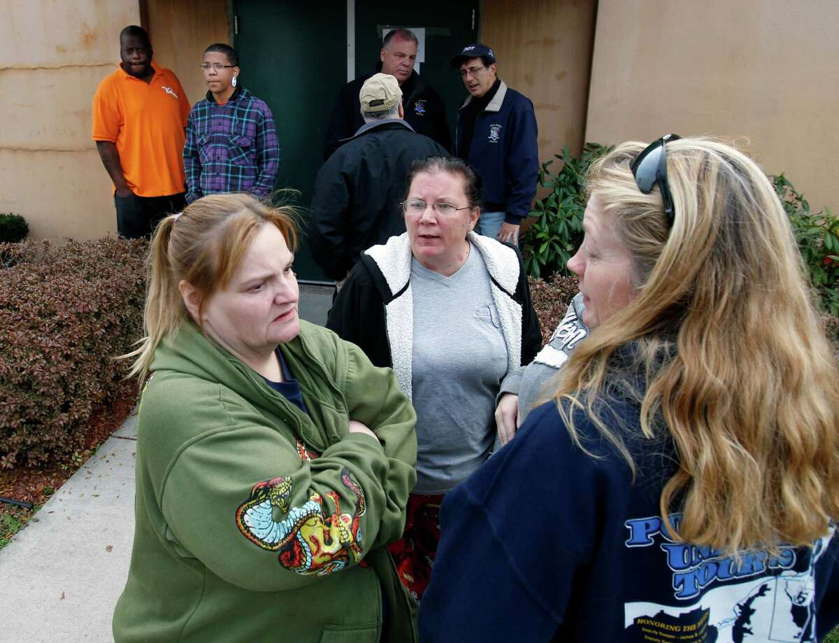 Displaced residents wait for a shuttle bus outside a fire hall and community center in Paulsboro, N.J., Saturday, Dec. 1, 2012, as more than 100 people remain out of their homes while officials continued efforts to clear a hazardous gas that spewed from a ruptured freight train car. The precautionary evacuations were ordered late Friday, hours after a train derailment. The order came after readings showed higher levels of vinyl chloride in the air.