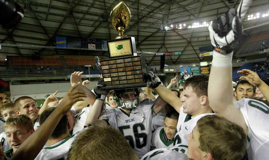 Skyline's Eric Wagner (56) celebrates with the trophy after Skyline beat Bellermine 49-24 to win the 4A division high school state championship football game, Saturday, Dec. 1, 2012, in Tacoma, Wash. Photo: Ted S. Warren / Associated Press