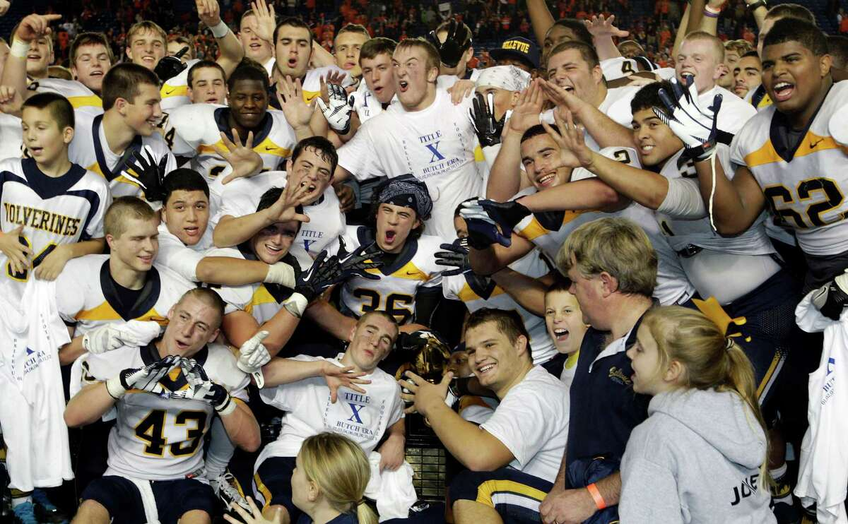 Bellevue players and coaches hold up five fingers as they celebrate with the trophy after they beat Eastside Catholic, 35-3 to win the 3A division high school state championship football game, for the fifth time in a row, Friday, Nov. 30, 2012, in Tacoma, Wash.
