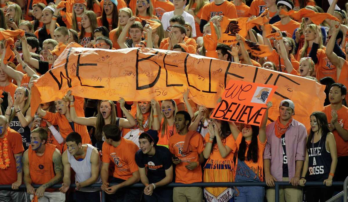 Eastside Catholic fans cheer as they hold a signs that read