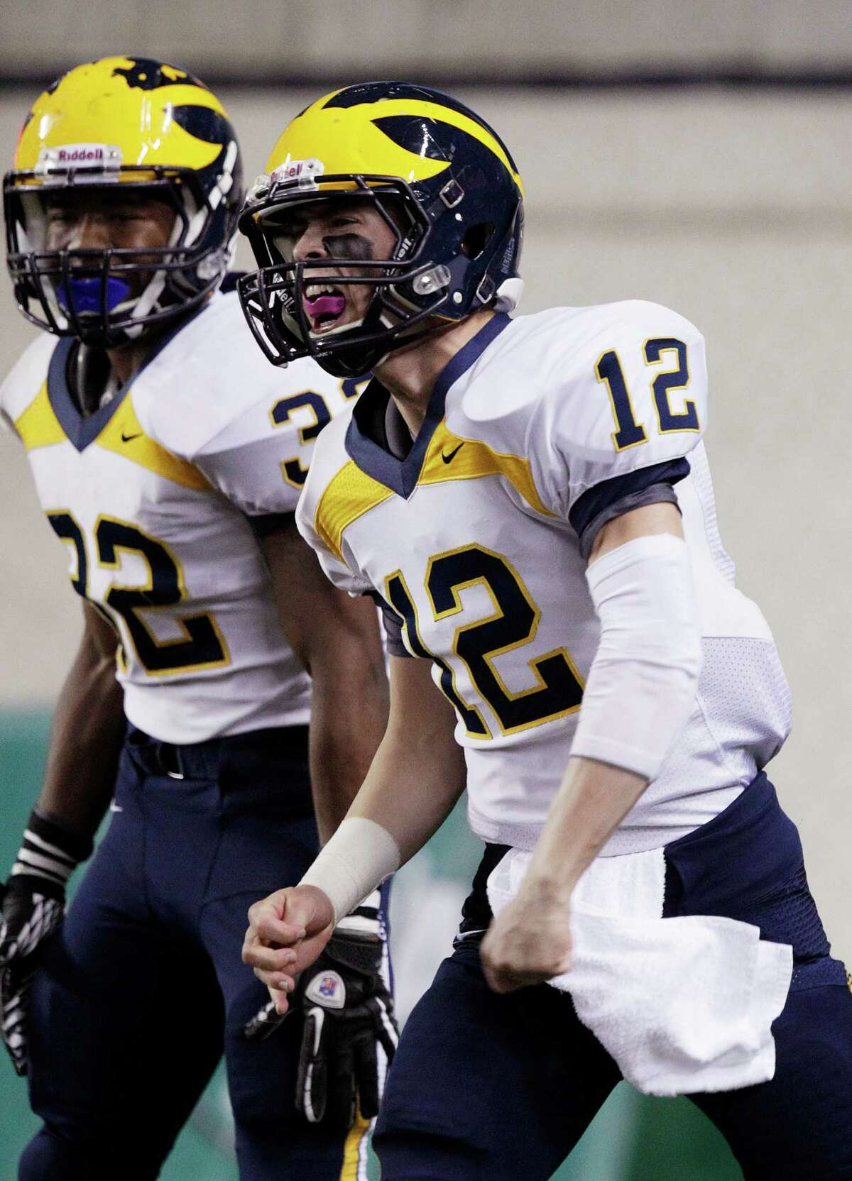 Bellevue quarterback Jack Meggs (12) celebrates with Budda Baker (32) after Meggs scored a touchdown in the first half against Eastside Catholic in the 3A division high school state championship football game, Friday, Nov. 30, 2012, in Tacoma, Wash.