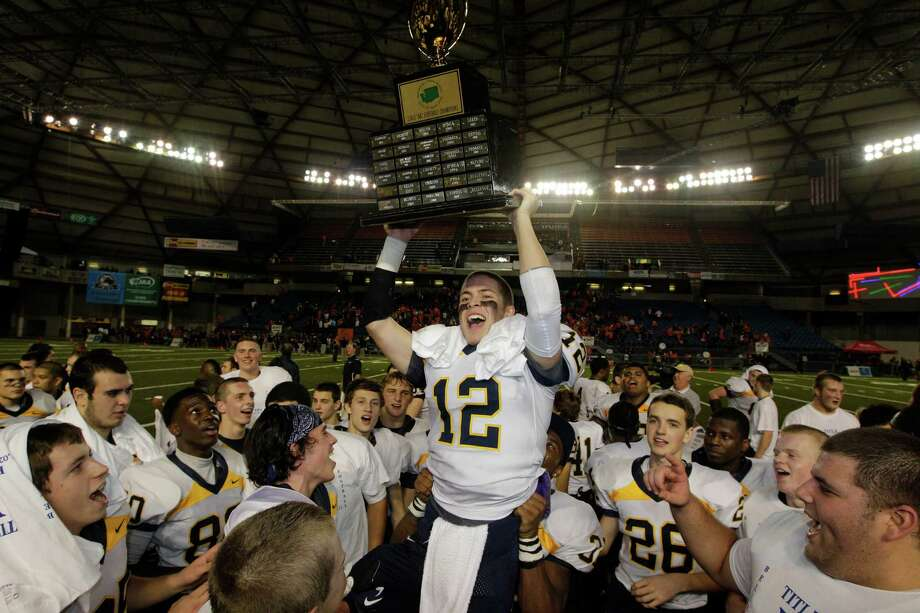 Bellevue quarterback Jack Meggs (12) lifts the trophy as he celebrates with teammates after Bellevue beat Eastside Catholic, 35-3 to win the 3A division high school state championship football game, Friday, Nov. 30, 2012, in Tacoma, Wash. Photo: Ted S. Warren / Associated Press