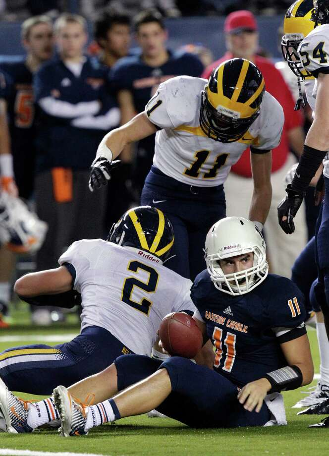 Eastside Catholic quarterback Trey Reynolds (11) gets up after being tackled by Bellevue's Timmy Haehl (11) and Michael Carlson (2) on a keeper play in the first half of the 3A division high school state championship football game, Friday, Nov. 30, 2012, in Tacoma, Wash. Photo: Ted S. Warren / Associated Press