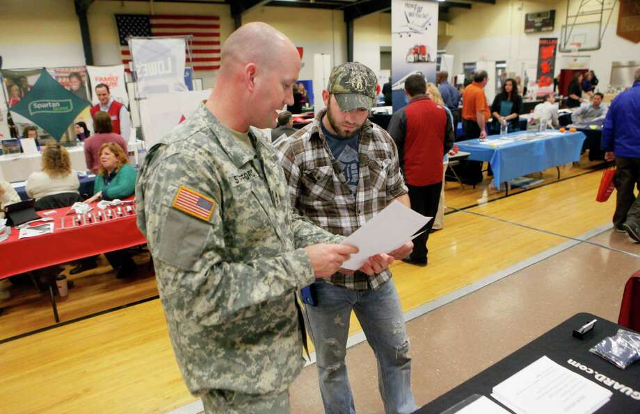 Jacob Hemry of Cedar Springs, Mich. (right) talks with Army National Guardsman David Stafford at Operation Vet Connection 2012 in Wyoming, Mich. As the war winds down, more veterans will need jobs. Photo: Emily Zoladz, Associated Press / The Grand Rapids Press