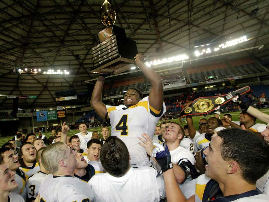 Bellevue's Myles Jack (4) lifts the trophy as he celebrates with teammates after Bellevue beat Eastside Catholic, 35-3 to win the 3A division high school state championship football game, Friday, Nov. 30, 2012, in Tacoma, Wash. Photo: Ted S. Warren / Associated Press