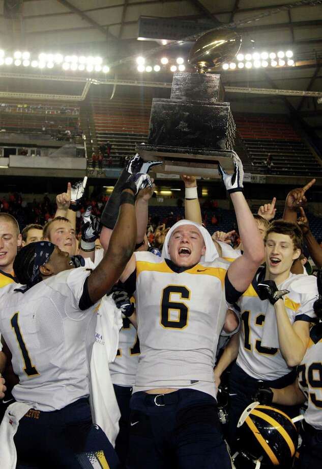Bellevue's Sean Constantine (6) lifts the trophy as he celebrates with teammates after Bellevue beat Eastside Catholic, 35-3 to win the 3A division high school state championship football game, Friday, Nov. 30, 2012, in Tacoma, Wash. Photo: Ted S. Warren / Associated Press