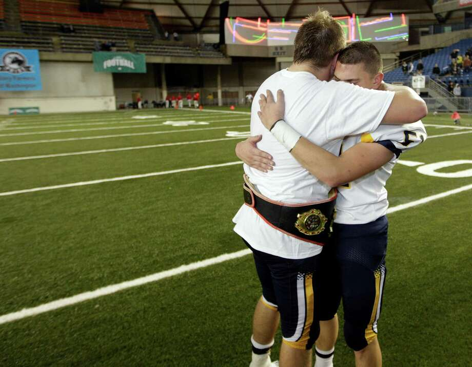 Bellevue's Nick Santa, left, hugs teammate Rio Morales, right, after Bellevue beat Eastside Catholic, 35-3 to win the 3A division high school state championship football game, for the fifth time in a row, Friday, Nov. 30, 2012, in Tacoma, Wash. Photo: Ted S. Warren / Associated Press