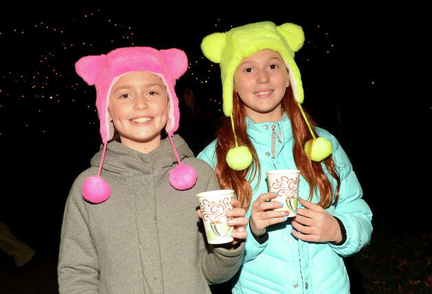 Phoebe Naylor, 9, of Rowayton, and Lexi Pepe, 9, of New Canaan, stay warm with neon colored fuzzy hats and hot cocoa during the annual Light up Rowayton holiday town lighting at Pinkney Park in Rowayton on Sunday, Dec. 2, 2012. Photo: Amy Mortensen / Connecticut Post Freelance