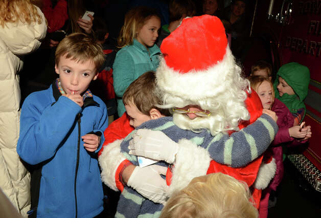 Michael Schneider, 6, of Rowayton, hugs Santa as his brother, John Schneider, 7, at left, waits in line during the annual Light up Rowayton holiday town lighting at Pinkney Park in Rowayton on Sunday, Dec. 2, 2012. Photo: Amy Mortensen / Connecticut Post Freelance