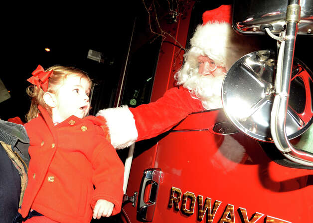 Annabelle Lifton, 2, of Darien, is greeted by Santa from the inside of a firetruck during the annual Light up Rowayton holiday town lighting at Pinkney Park in Rowayton on Sunday, Dec. 2, 2012. Photo: Amy Mortensen / Connecticut Post Freelance