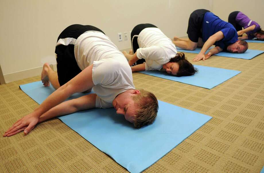 Tauk employees, including, from left, Billy Byrne, Edel Kollar, Chris Greco, and Linda Cortright, do yoga during the day on Thursday, November 29, 2012, as part of a wellness program promoted by the company. Photo: Lindsay Niegelberg / Stamford Advocate