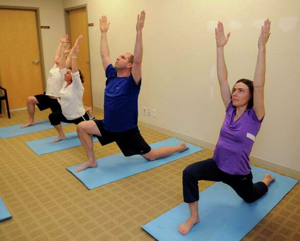 Tauk employees do yoga during the day on Thursday, November 29, 2012, as part of a wellness program promoted by the company. Photo: Lindsay Niegelberg / Stamford Advocate