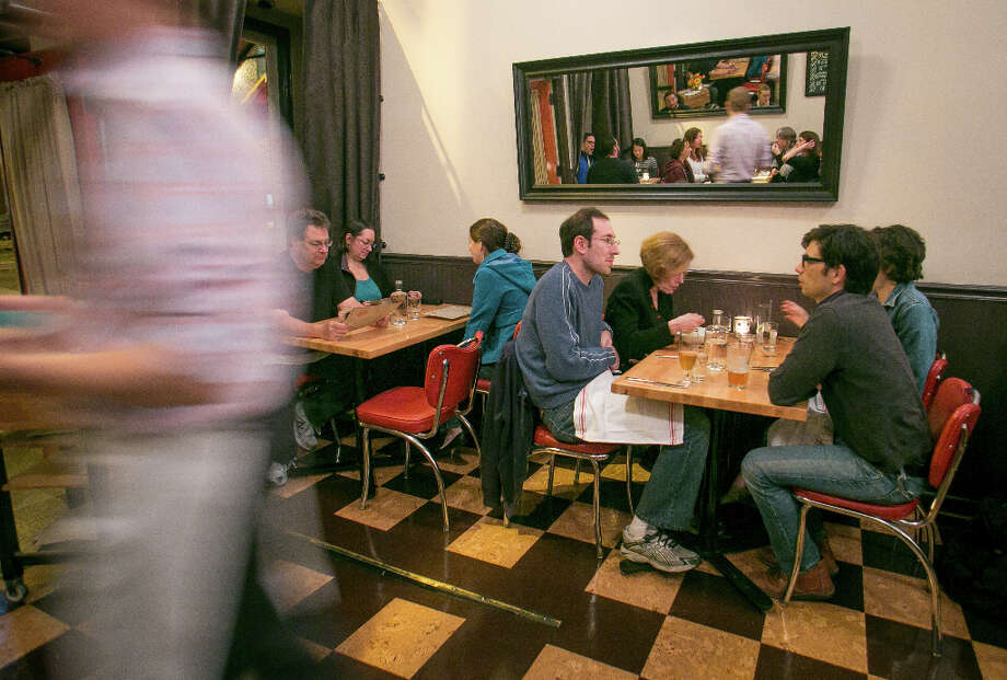 It serves American regional fare, which goes with the red chairs and stools and checkerboard-patterned floor, but there's a subtle Japanese influence in many dishes. Photo: John Storey, Special To The Chronicle / John Storey