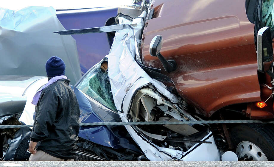 A man walks past the remnants of what Charles Sonnier, chief of the Labelle-Fannett Volunteer Fire Department, said is the white Chevrolet SUV that a Pearland couple was killed in during the Thanksgiving Day pileup on Interstate 10.   Photo taken Thursday, November 22, 2012 Guiseppe Barranco/The Enterprise Photo: Guiseppe Barranco, STAFF PHOTOGRAPHER / The Beaumont Enterprise