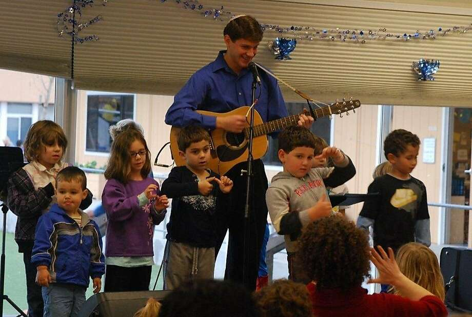Kids join guitarist Zach Ragent onstage in a sing-along at last year's Latkepalooza at the Jewish Community Center in Foster City. Photo: Eileen Mitchell