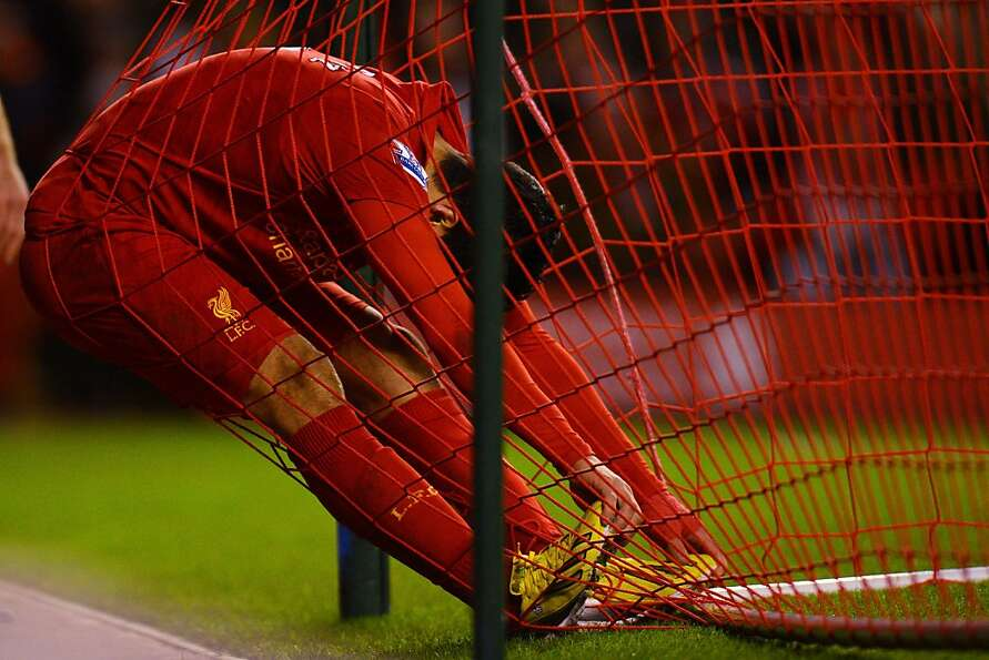 He meshed up: Liverpool's Luis Suarez falls into the net after missing on a good scoring chan