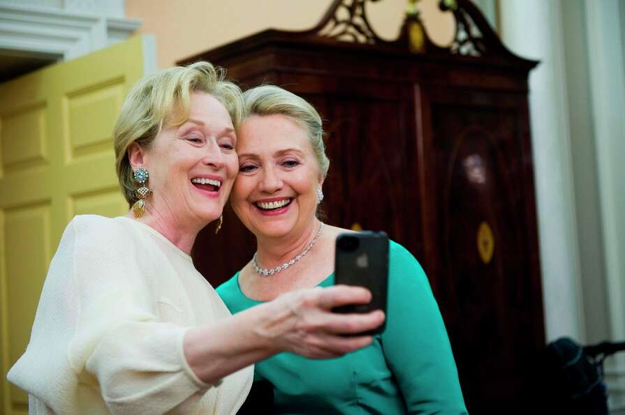 Actress Meryl Streep uses her iPhone to get a photo of her and Secretary of State Hillary Rodham Cli