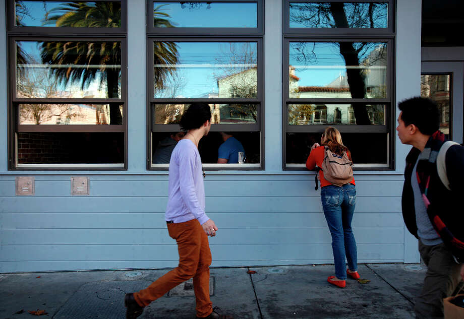 People stop to check the score of the 49ers game while walking by. Photo: Sarah Rice, Special To The Chronicle / ONLINE_YES