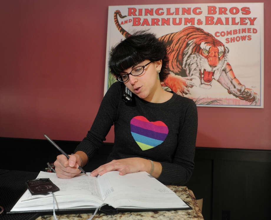Ashley Wacker, hostess at the Barnum Publick House, takes a reservation over the phone for a party of twelve coming to Bridgeport for dinner on Tuesday, prior to the Neil Young & Crazy Horse concert scheduled at the Webster Bank Arena. Photo: Ned Gerard / Connecticut Post