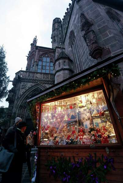 Visitors look at Christmas decorations for sale at the traditional Christmas market 'Nuernberger Chr