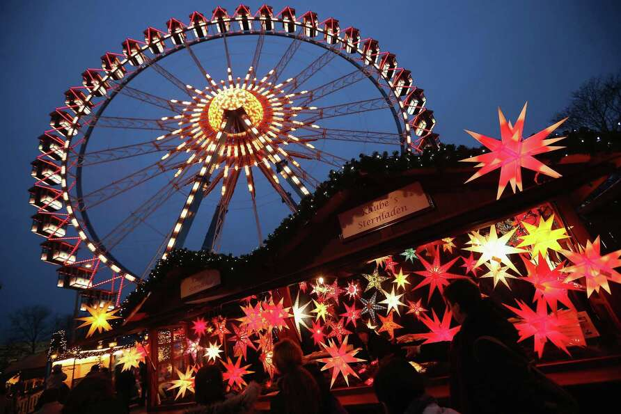 Visitors walk past a stall selling illuminated Christmas stars at the annual Christmas market at Ale