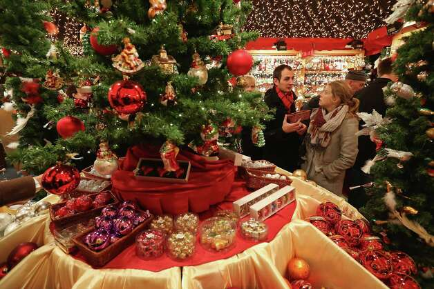 Visitors look at Christmas decorations for sale at the Kaethe Wohlfahrt stand at the annual Christmas market at Gendarmenmarkt on its opening day on November 26, 2012 in Berlin, Germany. Christmas markets, with their stalls selling mulled wine, Christmas tree decorations and other delights, are an integral part of German Christmas tradition, and many of them opened across Germany today. Photo: Sean Gallup, Getty Images / 2012 Getty Images