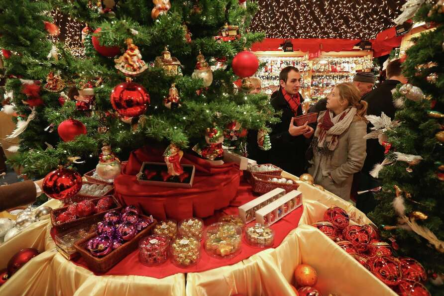 Visitors look at Christmas decorations for sale at the Kaethe Wohlfahrt stand at the annual Christma