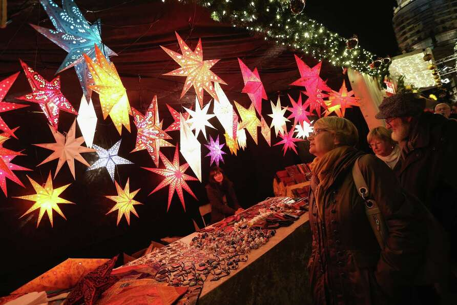 Visitors look at illuminated Christmas starts for sale at the annual Christmas market at Gendarmenma