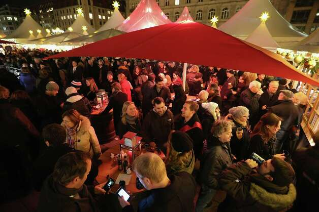 Visitors crowd a mulled wine stand at the annual Christmas market at Gendarmenmarkt on its opening day on November 26, 2012 in Berlin, Germany. Christmas markets, with their stalls selling mulled wine (Gluehwein), Christmas tree decorations and other delights, are an integral part of German Christmas tradition, and many of them opened across Germany today. Photo: Sean Gallup, Getty Images / 2012 Getty Images