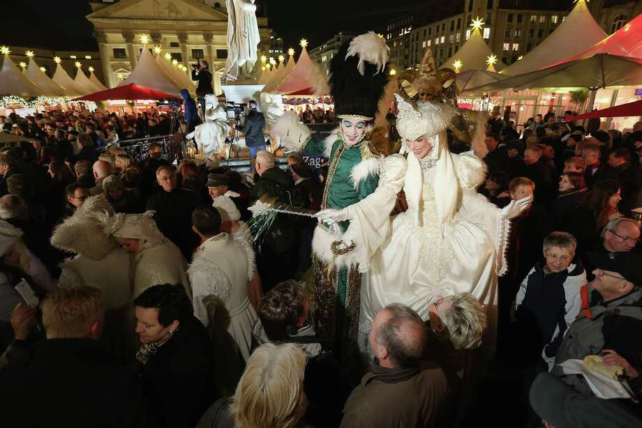 Performers on stilts walk among visitors at the annual Christmas market at Gendarmenmarkt on its opening day on November 26, 2012 in Berlin, Germany. Christmas markets, with their stalls selling mulled wine, Christmas tree decorations and other delights, are an integral part of German Christmas tradition, and many of them opened across Germany today. Photo: Sean Gallup, Getty Images / 2012 Getty Images