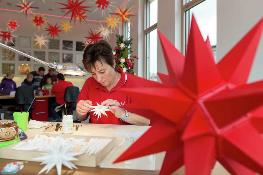 An employee at the Herrnhuter Sterne Christmas stars factory assembles Christmas stars that will dec