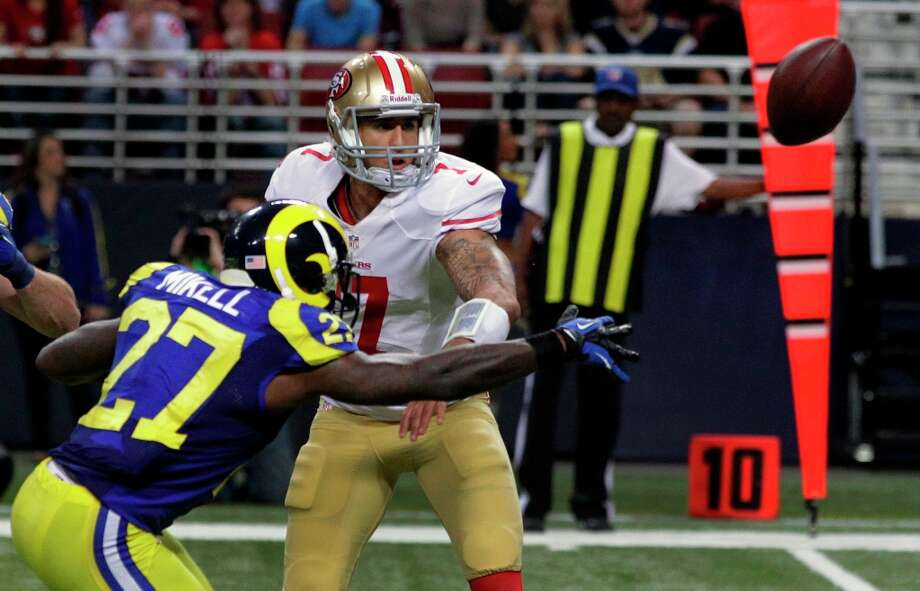 San Francisco 49ers quarterback Colin Kaepernick, right, tries to toss the ball to teammate Ted Ginn as St. Louis Rams' Quintin Mikell (27) defends during the second half of an NFL football game on Sunday, Dec. 2, 2012, in St. Louis. The play was ruled a fumble, recovered by Rams' Janoris Jenkins who took it in for a touchdown. Photo: Seth Perlman, Associated Press / AP