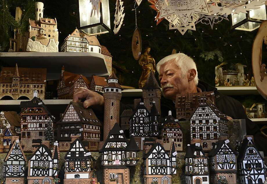 "A vendor selling small decorative houses prepares his stand of the traditional Christmas Market in Nuremberg, southern Germany, on November 30, 2012. The traditional ""Nuernberger Christkindlesmarkt"" opens from November 30 to December 24, 2012. Photo: Christof Stache, AFP/Getty Images"