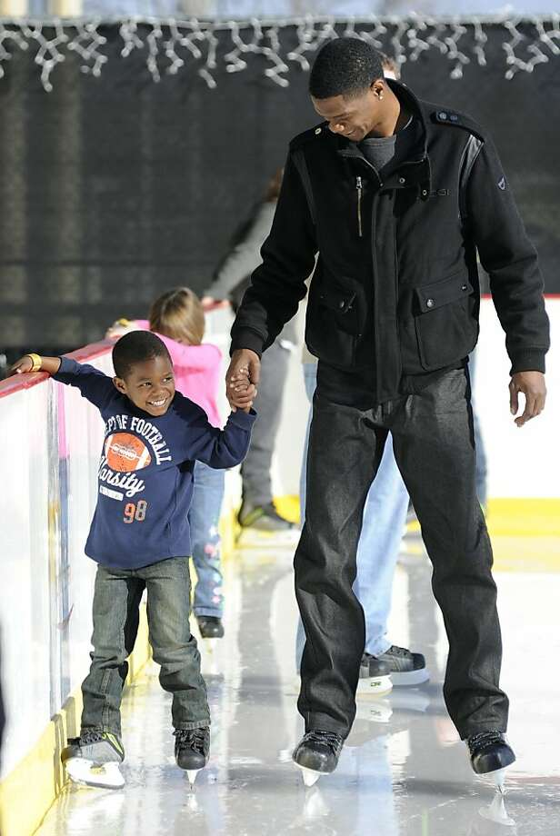 First day ever on skates: Wobbly 4-year-old Tyler Cady holds onto dad Courtney and the edge of the rink at Winterfest in Raleigh, N.C. Photo: Liz Condo, Associated Press