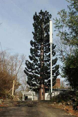 "The new cell tower, ""the tree,"" left, and the Verizon Wireless, in Byram, Conn., Monday, Dec. 3, 2012. A Byram resident is angered at the work done by a Verizon Wireless contractor at the site of the new cell tower at 36 Ritch Avenue West John Hartwell is angry that Verizon has still failed to take down the previous tower on the site and at the work down on the driveway leading up to the new tower that negatively impacted his property. He is opposing a request by Verizon Wireless for an extension by the carrier to complete the work. The request is in front of the Connecticut Siting Council. Photo: Helen Neafsey / Greenwich Time"